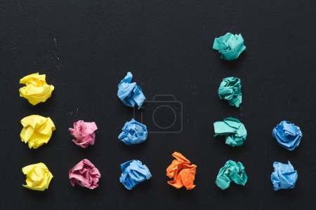 top view of arranged colorful crumpled paper balls on black background, think different concept