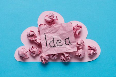 top view of pink cardboard cloud with crumpled paper balls and 'idea' word written on sticky note on blue background, ideas concept