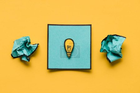 crumpled paper and note with light bulb drawing on yellow background, ideas concept