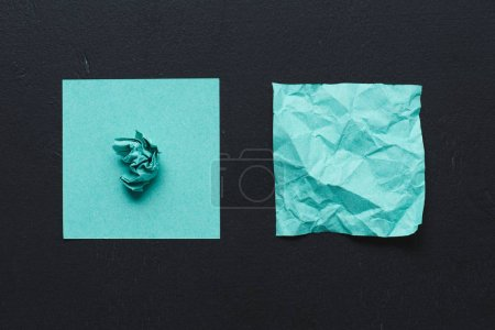 top view of turquoise crumpled paper on black background, think different concept