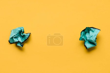 top view of crumpled paper balls with copy space on yellow background, think different concept