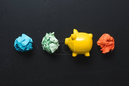 top view of colorful crumpled paper balls with piggy bank on black background, insurance concept