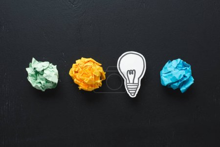 Photo for Top view of colorful crumpled paper balls and light bulb drawing on black background, ideas concept - Royalty Free Image