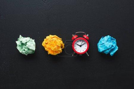 Photo pour Vue de dessus des boules de papier froissé coloré et horloge sur fond noir, concept de gestion de temps - image libre de droit