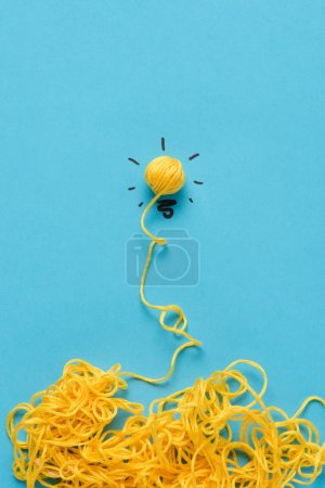 light bulb sign made of yellow yarn on blue background, ideas concept