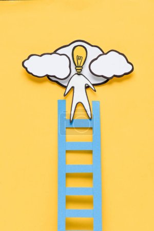Foto de Vista superior de cartón hombre con cabeza de bombilla de luz subiendo escalera sobre fondo amarillo, concepto de ideas - Imagen libre de derechos