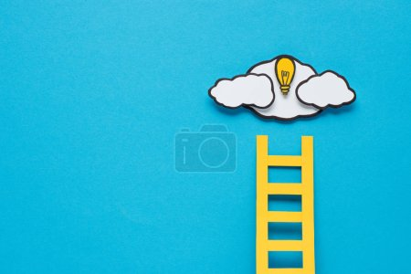cardboard ladder, light bulb and clouds with copy space on blue background, ideas concept
