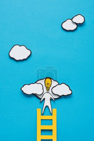 top view of cardboard man with light bulb head climbing ladder on blue background, ideas concept