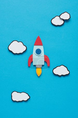 Photo for Top view of paper rocket with clouds on blue background, setting goals concept - Royalty Free Image