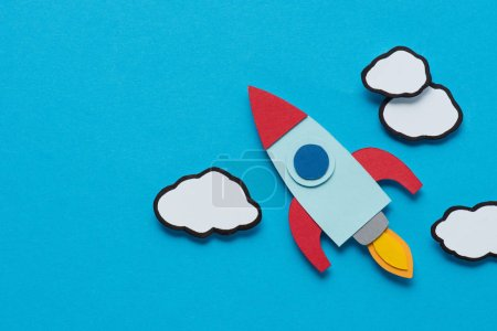 Photo for Top view of cardboard rocket with clouds on blue background, setting goals concept - Royalty Free Image