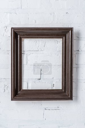 black empty frame hanging on white brick wall