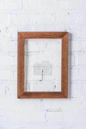 Photo for Brown empty frame hanging on white brick wall - Royalty Free Image