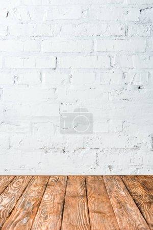 mur de briques blanches et table en bois