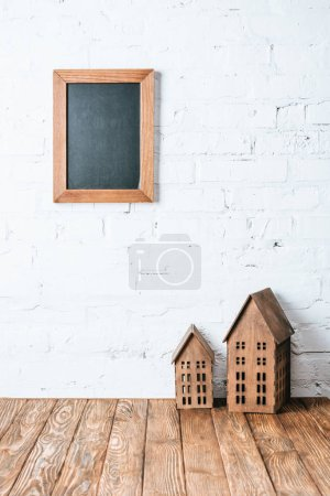 brown blank frame on white brick wall with rustic house models on wooden table