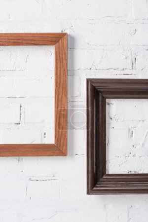 brown and black empty frames hanging on white brick wall