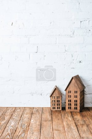 rustic house models on wooden table near white brick wall