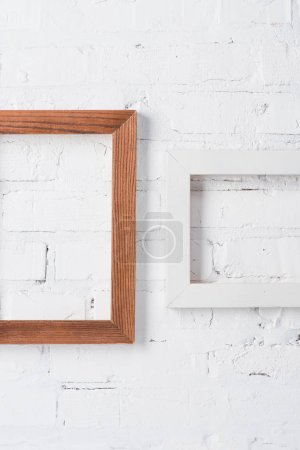 brown and white empty frames hanging on brick wall