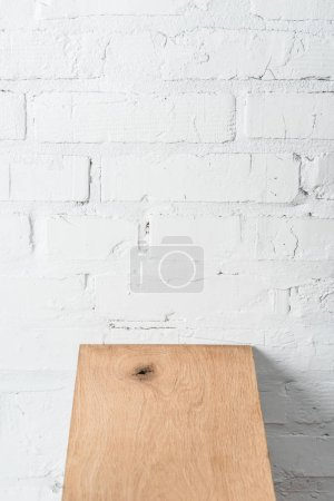 textured wooden board and white brick wall