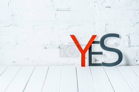 "Photo for ""yes"" lettering with decorative red and black letters on wooden table near white brick wall - Royalty Free Image"