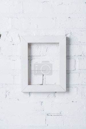 rustic frame hanging on white brick wall