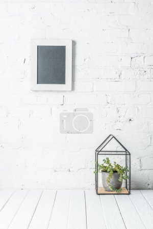 Photo for White blank frame on brick wall with plant in pot on rustic wooden table - Royalty Free Image