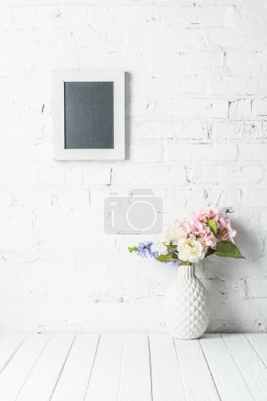 blank frame on white brick wall with bouquet in ceramic vase on rustic wooden table