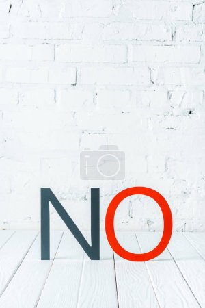 """""""no"""" lettering with decorative black and red letters on white wooden surface with brick wall at background"""