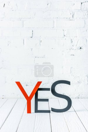 "Photo for ""yes"" lettering with decorative red and black letters on wooden surface with white brick wall at background - Royalty Free Image"