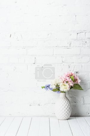 ceramic vase with flower bouquet on rustic wooden table near brick wall