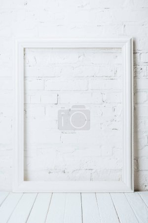 white empty frame on rustic wooden table near brick wall