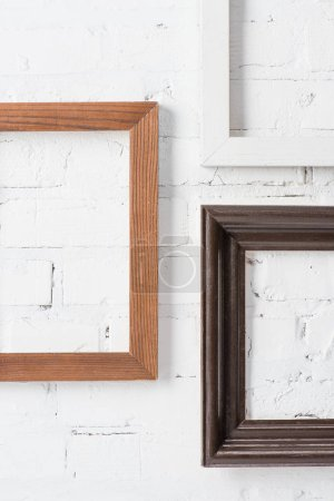 rustic multicolored empty frames hanging on white brick wall