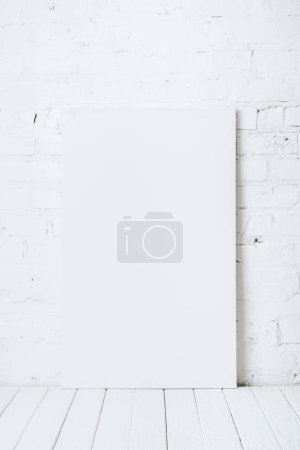 blank placard on white wooden table near brick wall