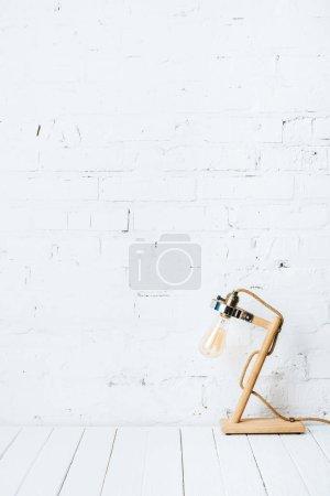 Foto de Lámpara de mesa en mesa de madera blanca junto a la pared de ladrillo - Imagen libre de derechos