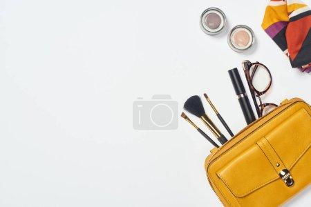 Photo pour Vue du dessus de l'écharpe, des lunettes, du mascara, des pinceaux cosmétiques, du fard à paupières et du sac sur fond blanc - image libre de droit