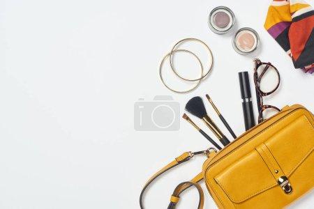 Photo pour Vue du dessus des bracelets, foulard, lunettes, mascara, pinceaux cosmétiques, fard à paupières et sac jaune - image libre de droit