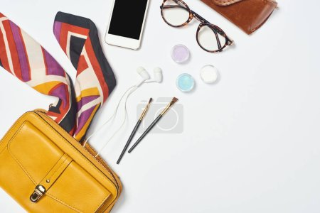 Photo for Bag, scarf, glasses, cosmetic brushes, case, earphones, eyeshadow and smartphone on white background - Royalty Free Image