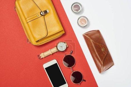 Photo pour Vue du dessus du sac, lunettes de soleil, fard à paupières, smartphone, montre et étui - image libre de droit