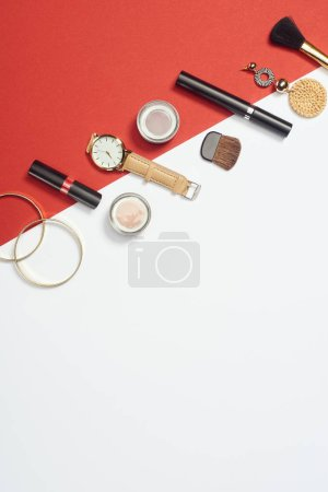 Flat lay with mascara, watch, lipstick, bracelets, eyeshadow, cosmetic brushes and earring