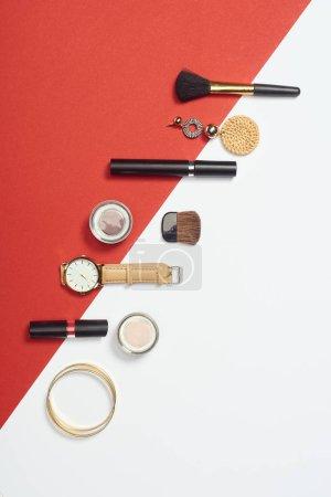 Photo pour Couché plat avec mascara, montre, bracelets, fard à paupières, rouge à lèvres, boucle d'oreille et pinceaux cosmétiques - image libre de droit