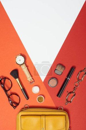 Photo pour Couché plat avec mascara, montre, sac jaune, bracelet, fard à paupières, fard à joues, lunettes et pinceaux cosmétiques - image libre de droit