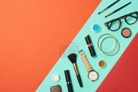 Photo for Mascara, watch, lipstick, bracelets, eyeshadow, blush, glasses and cosmetic brushes on turquoise background - Royalty Free Image