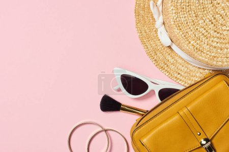 Photo for Top view of straw hat, bracelets, cosmetic brush, sunglasses and yellow bag on pink background - Royalty Free Image