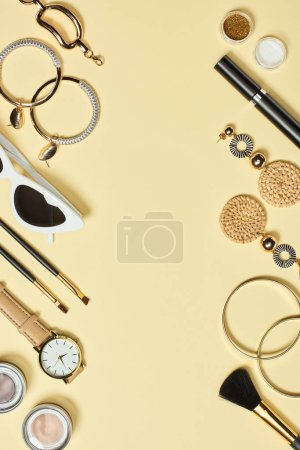 Watch, sunglasses, eyeshadow, cosmetic brushes, bracelets, earrings and mascara on yellow background