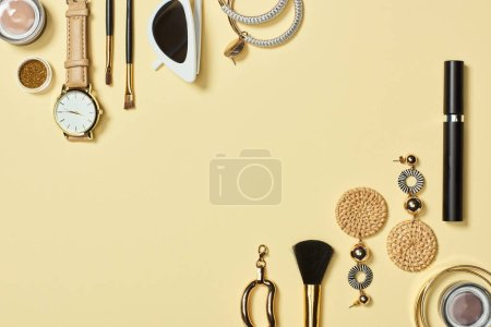 Photo for Top view of watch, sunglasses, eyeshadow, cosmetic brushes, bracelets, earrings and mascara on yellow background - Royalty Free Image