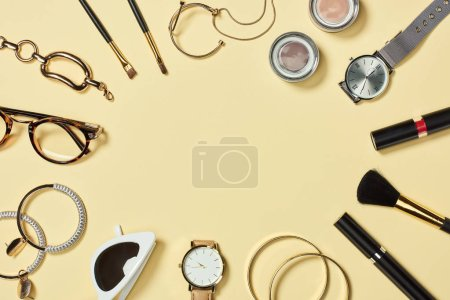 Photo for Top view of watches, lipstick, glasses, sunglasses, eyeshadow, blush, cosmetic brushes, bracelets, earrings and mascara on yellow background - Royalty Free Image