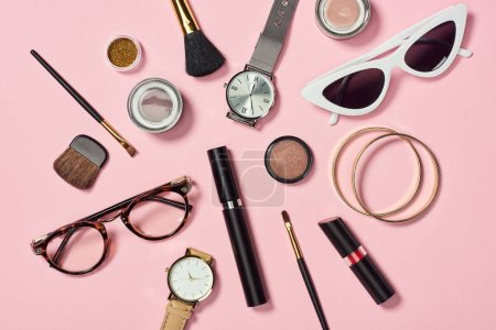 Photo for Top view of watches, lipstick, glasses, sunglasses, eyeshadow, blush, cosmetic brushes, bracelets and mascara on pink background - Royalty Free Image