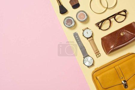 Photo pour Vue de dessus des pinceaux fard à paupières, des bracelets et des cosmétiques, cas, montres, lunettes, sac jaune - image libre de droit