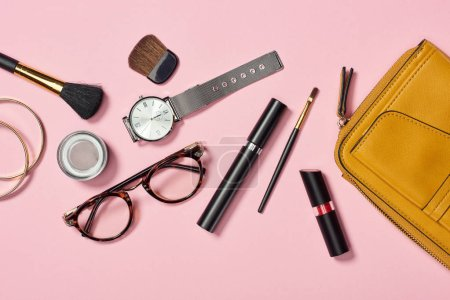Photo for Top view of watch, bag, lipstick, glasses, eyeshadow, bracelets, mascara and cosmetic brushes on white background - Royalty Free Image