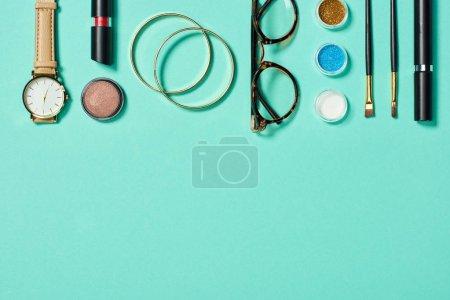 Photo pour Vue du dessus de la montre, rouge à lèvres, bracelets, lunettes, fard à paupières, blush, pinceaux cosmétiques et mascara sur fond turquoise - image libre de droit
