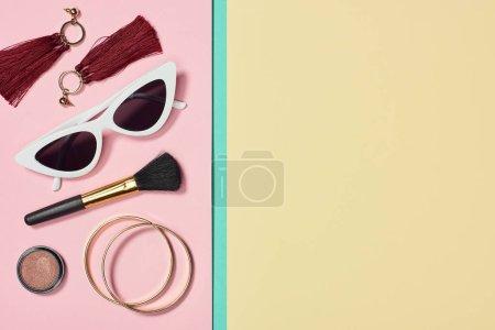 Photo pour Pose plate avec rouge à lèvres, bracelets, boucles d'oreilles, pinceau cosmétique, lunettes de soleil et blush - image libre de droit